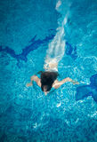 Woman covered in long white fabric swimming underwater at pool Stock Photography
