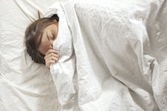 Woman covered with pillow. Sleeping in a white bed. Royalty Free Stock Image