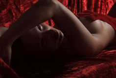Woman covered with red silk sheet Stock Photography