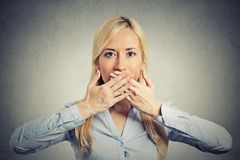 Woman covering closed mouth with hands Royalty Free Stock Photography