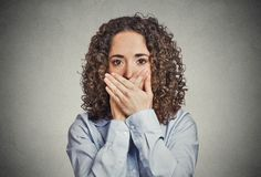 Woman covering closed mouth with hands. Speak no evil stock photography