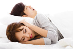 Woman covering ears  while  husband is snoring Stock Photo