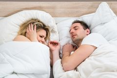 Woman covering ears while man snoring. In Bed At Home Stock Photo