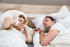 Woman covering ears while man snoring. In Bed At Home Royalty Free Stock Photos