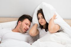 Woman covering ears while man snoring on bed at home Stock Photos