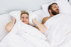 Woman covering ears while man snoring on bed. Woman covering ears while men snoring on bed at home Stock Images