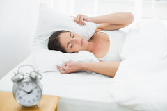 Woman covering ears with pillow and alarm clock on side table Royalty Free Stock Image