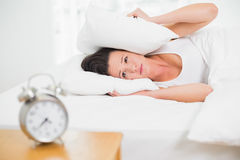 Woman covering ears with pillow and alarm clock on side table Stock Photography