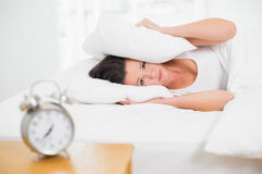 Woman covering ears with pillow and alarm clock on side table Stock Photo