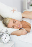 Woman covering ears with pillow and alarm clock on table Stock Images