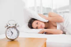 woman covering ears with pillow in bed and alarm clock on table Royalty Free Stock Photos