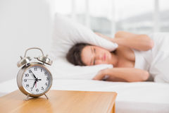 Woman covering ears with pillow in bed and alarm clock on table Stock Photo