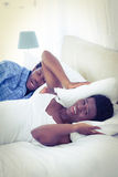 Woman covering ears with pillow while her husband is snoring. On bed Stock Photos