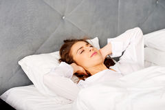 Woman covering ears with pillow because of noise. Insomnia concept royalty free stock image