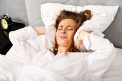 Woman covering ears with pillow because of noise. Insomnia concept stock image