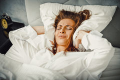 Woman covering ears with pillow because of noise. Stock Image