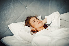 Woman covering ears with pillow because of noise. Stock Photo