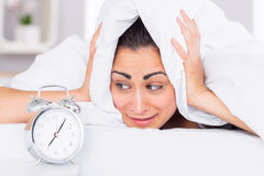 Woman covering ears with sheet in bed Stock Images