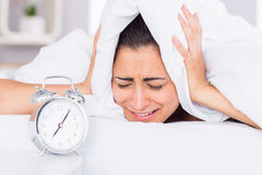 Woman covering ears with sheet in bed Royalty Free Stock Photos