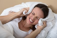 Woman Covering Ears To Shut Out Noise. Troubled Woman In Bed Covering Ears To Shut Out Noise royalty free stock photography