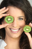 Woman covering eye with kiwi Stock Photo