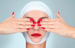 Beauty, Fashion and Plastic Surgery concept. Woman covering eyes with bandaged head. Woman covering eyes with bandaged head. Beauty, Fashion and Plastic Surgery stock photos