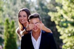 Woman covering the eyes of a man Stock Photography