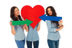 Woman covering face with a big heart , friends pointing arrows Royalty Free Stock Image