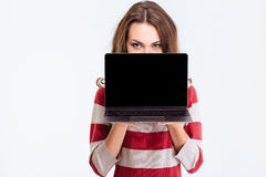 Woman covering face with blank laptop computer screen. Portrait of a young woman covering face with blank laptop computer screen isolated on a white background Stock Image