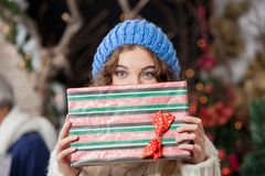 Woman Covering Face With Christmas Present At Stock Image