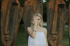 Woman Covering Face With Right Hand in Front of Large Tribal Head Statue Royalty Free Stock Photos