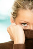 Woman covering face with turtleneck Stock Images