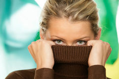 Woman covering face with turtleneck Stock Image