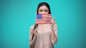 Woman covering face with USA flag, learning language, education and travel. Stock footage stock video footage