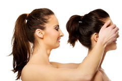 Woman covering friend's eyes. Royalty Free Stock Images