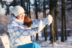 Woman covering by hands from sunlight in winter park Royalty Free Stock Image