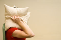 Woman covering head with a pillow Stock Photo
