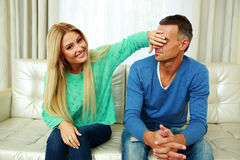 Woman covering her boyfriend`s eyes Stock Images