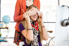 Woman covering her colleague eyes from behind Royalty Free Stock Photography