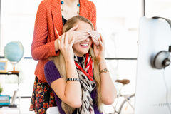 Woman covering her colleague eyes from behind Royalty Free Stock Photos