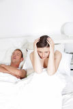 Woman covering her ears as her husbands snores Stock Image