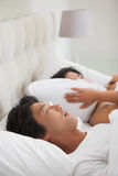 Woman covering her ears as partner is snoring loudly. At home in bedroom Royalty Free Stock Image