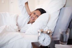 Woman covering her ears cause of ringing alarm clock. Young woman covering her ears cause of ringing alarm clock Royalty Free Stock Photography