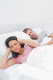 Woman covering her ears while her husband is snoring. Next to her Stock Photos