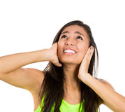 Woman covering her ears looking up, as if to say, stop making that loud noise it's giving me a headache, Royalty Free Stock Image