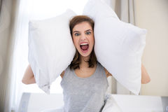 Woman covering her ears with pillows Royalty Free Stock Image