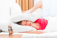 Woman covering her ears pillows Royalty Free Stock Images
