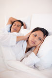 Woman covering her ears to block her boyfriends snoring Stock Photos
