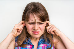 Woman covering her ears to protect from loud noise. Stressed woman covering her ears to protect from loud noise  on white Stock Photography