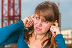 Woman covering her ears to protect from loud noise. Unhappy woman covering her ears to protect from loud noise royalty free stock photos